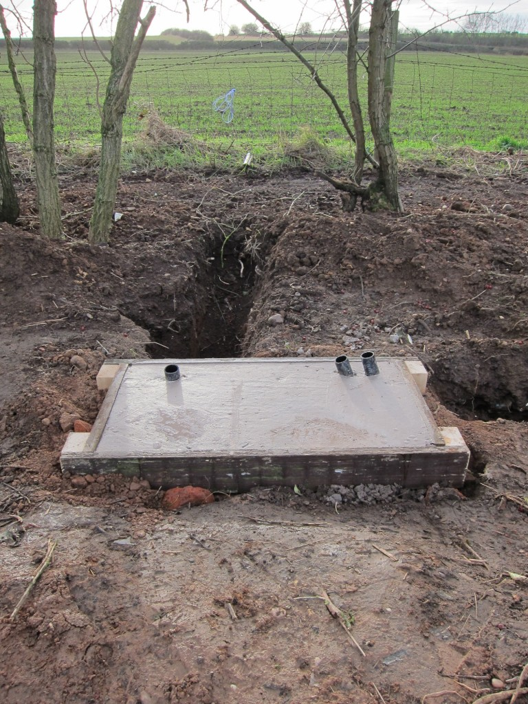 Prepared concrete pad with embedded electrical cable duct ready for installation of GRP cabinet.