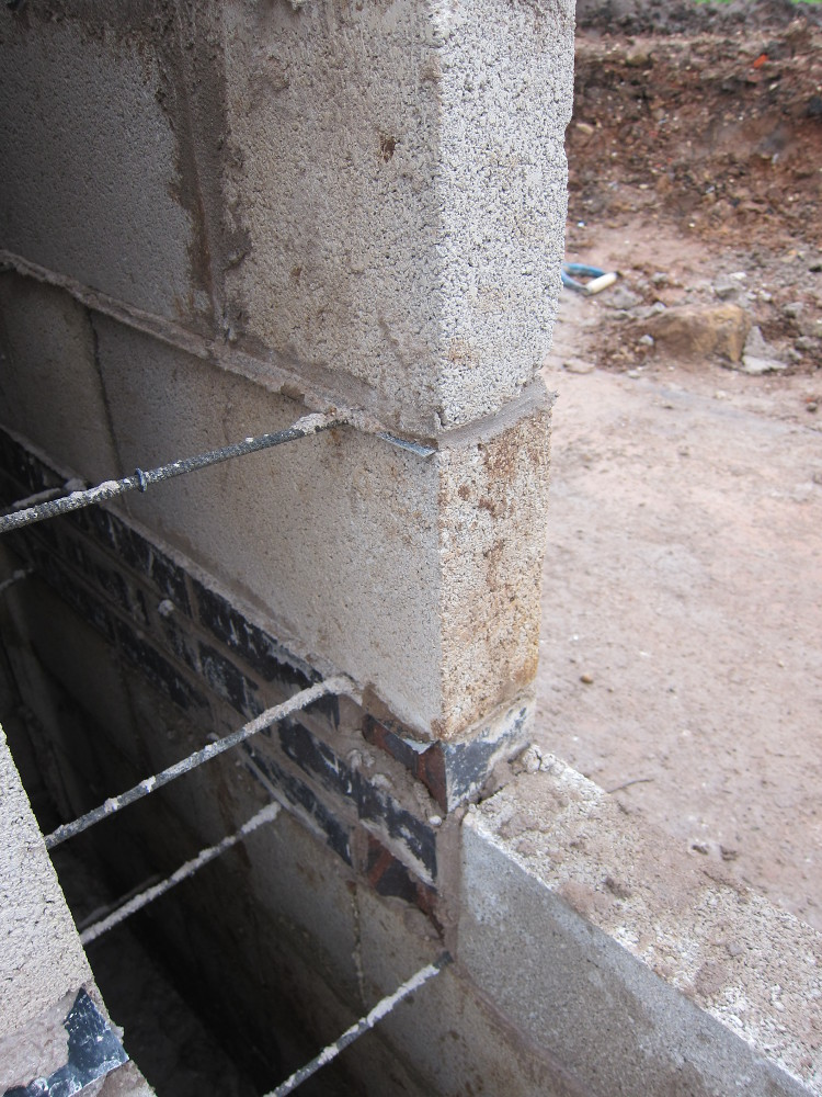 "The ""double damp"" - two layers of damp-proof-course membrane, one immediately above the blue bricks and one just visible above the first block - which gives the option to bring the external ground level up to the top of the blue bricks to match the internal floor level"