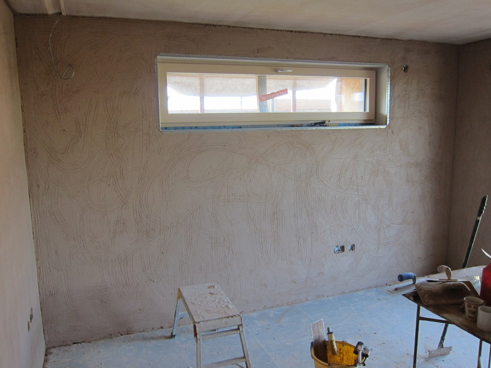 Base coat of wet plaster on the masonry outer wall in Bedroom 3
