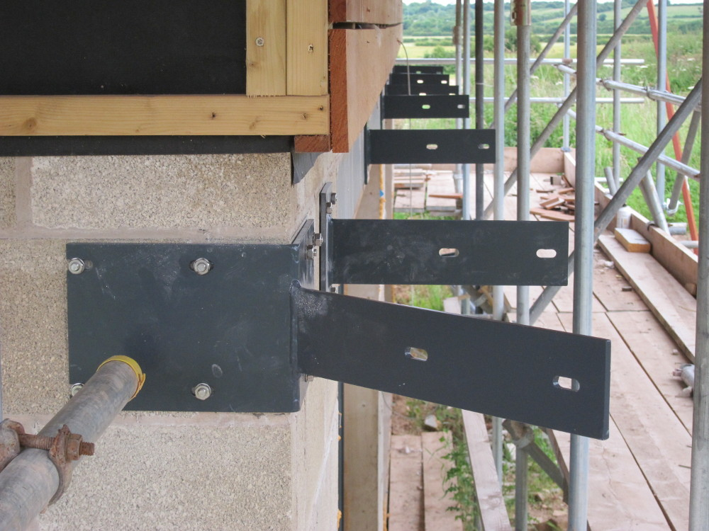 Steel support brackets for Contrasol brise soleil above sliding doors on the south and west elevations