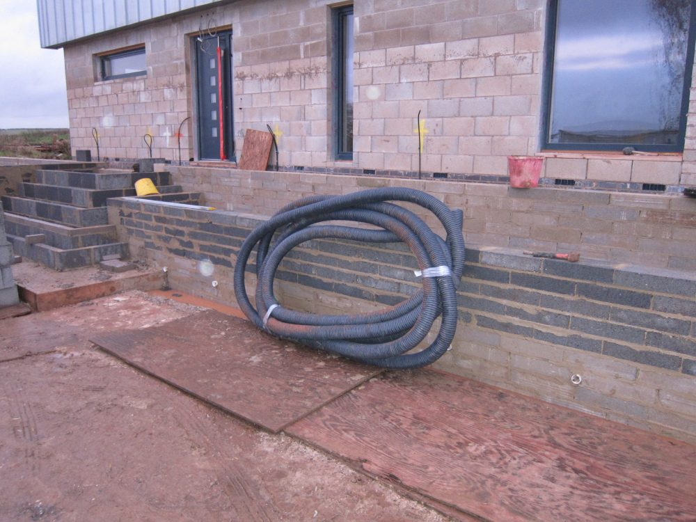 Perforated pipe ready for installation behind the retaining wall